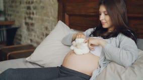 La jeune dame enceinte tient les chaussures de bébé adorables dans des mains et fait de petites étapes sur son ventre jouant avec clips vidéos