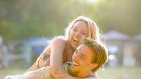 La jeune dame gaie équipe dessus de retour, les couples de sourire ayant l'amusement dehors, amitié Photo libre de droits