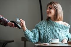 La jeune dame gaie paye son ordre avec la carte de débit Images stock