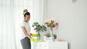 La jeune dame heureuse écoute la musique par des écouteurs et dansant pendant le nettoyage dans le studio moderne, la fille se ti clips vidéos