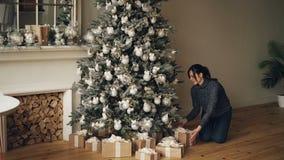 La jeune dame heureuse met des présents sous l'arbre admirablement décoré de nouvelle année regardant alors des boîte-cadeau et l banque de vidéos