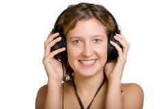 La jeune dame souriante est écoutent la musique Photos libres de droits