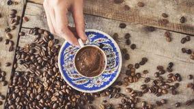 La jeune dame tenant le grain de café de café turc rapièce le fond en bois Photo stock