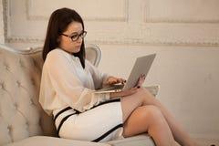 La jeune dame travaille sur l'ordinateur portable à confortable Images libres de droits