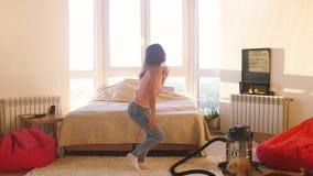 La jeune danse insouciante heureuse de femme de brune dans la chambre à coucher avec la grande fenêtre écoute la musique ayant l' banque de vidéos