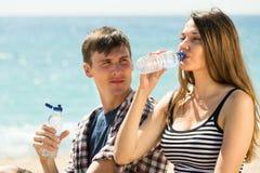 La jeune eau de boissons de couples Photos stock