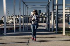 La jeune et attirante femme marche le long du chemin en parc industriel dans le forum de port, Barcelone, Espagne Photo stock