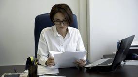La jeune et belle femme d'affaires avec les cheveux courts et foncés dans la chemise blanche est fatiguée du travail dans le bure photographie stock