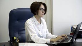 La jeune et belle femme d'affaires avec les cheveux courts et foncés dans la chemise blanche est fatiguée du travail dans le bure photo stock