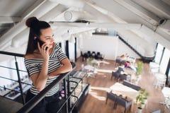 La jeune et belle femme parle au téléphone portable au café, à la communication ou au concept occasionnel de mode de vie de café Photographie stock libre de droits