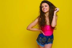 La jeune et belle fille bouclée dans une chemise et un bleu roses court-circuite o Image stock