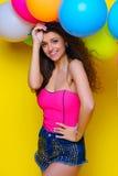 La jeune et belle fille bouclée dans une chemise et un bleu roses court-circuite o Image libre de droits