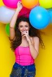 La jeune et belle fille bouclée dans une chemise et un bleu roses court-circuite o Photographie stock libre de droits