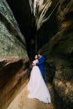 La jeune et romantique jeune mariée avec son marié affectueux posant dans l'obscurité a survécu à la fissure de roche Images stock