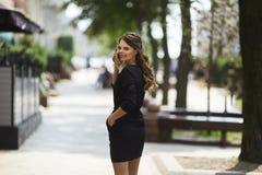 La jeune et souriante femme d'affaires dans une robe noire élégante va à une réunion par la rue de ville d'été images stock