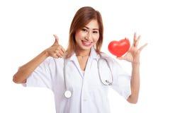 La jeune exposition femelle asiatique de docteur manie maladroitement avec le coeur rouge Photographie stock