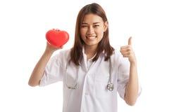 La jeune exposition femelle asiatique de docteur manie maladroitement avec le coeur rouge Photo stock
