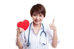 La jeune exposition femelle asiatique de docteur manie maladroitement avec le coeur rouge Photo libre de droits