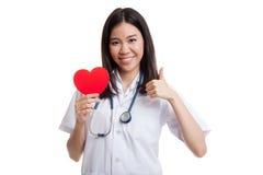 La jeune exposition femelle asiatique de docteur manie maladroitement avec le coeur rouge Images libres de droits
