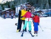 La jeune famille active apprécie des sports d'hiver dans la station de vacances suisse avec du charme des Saas-honoraires Photographie stock libre de droits