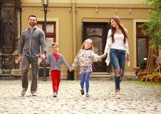 La jeune famille avec des enfants marchent dessus la rue de la ville de touristes images libres de droits