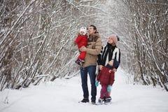 La jeune famille avec des enfants marchent en parc d'hiver Winte Photos libres de droits