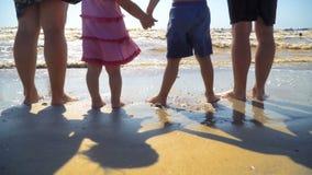 La jeune famille avec des enfants se tiennent sur la plage tenant des mains et regardant la mer banque de vidéos