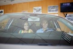 La jeune famille choisissent la nouvelle voiture dans une salle d'exposition Bille 3d différente Photo stock
