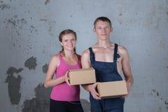 La jeune famille de deux personnes affectueuses analyse des boîtes dans le nouvel apartm Photographie stock