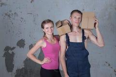La jeune famille de deux personnes affectueuses analyse des boîtes dans le nouvel apartm Photographie stock libre de droits