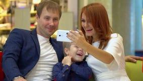 La jeune famille est photographiée tous ensemble Un selfie avec des achats pour Noël Beaux ajouter à l'enfant dedans banque de vidéos