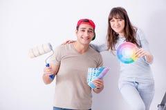 La jeune famille faisant des murs de peinture de rénovation à la maison - image libre de droits