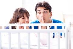 La jeune famille heureuse au berceau de lit de bébé Images stock