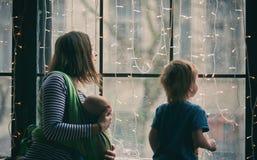 La jeune famille heureuse, la belle mère avec deux enfants, le garçon préscolaire adorable et le bébé dans la bride regardent ens Images libres de droits