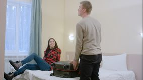 La jeune famille heureuse entrant dans une chambre d'hôtel et déballent le bagage Images stock