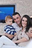 La jeune famille heureuse ont l'amusement avec la TV dans le backgrund Images stock