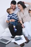 La jeune famille heureuse ont l'amusement avec la TV dans le backgrund Photos libres de droits