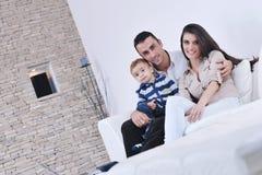 La jeune famille heureuse ont l'amusement avec la TV dans le backgrund Photo libre de droits