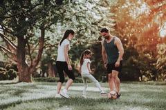 La jeune famille heureuse ont l'amusement extérieur dans le parc d'été image libre de droits