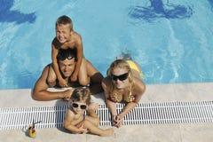 La jeune famille heureuse ont l'amusement sur la piscine Image libre de droits