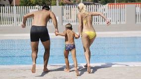 La jeune famille heureuse ont l'amusement sur la piscine Images stock