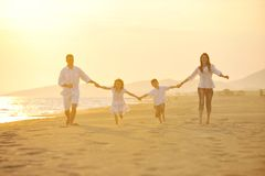 La jeune famille heureuse ont l'amusement sur la plage au coucher du soleil Photo libre de droits