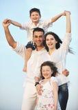 La jeune famille heureuse ont l'amusement sur la plage au coucher du soleil Photographie stock