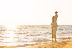La jeune famille heureuse ont l'amusement sur la plage courue et sautent au coucher du soleil Photographie stock