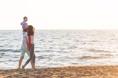 La jeune famille heureuse ont l'amusement sur la plage courue et sautent au coucher du soleil Photo libre de droits