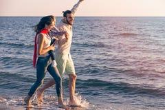 La jeune famille heureuse ont l'amusement sur la plage courue et sautent au coucher du soleil Photos stock