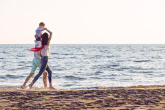 La jeune famille heureuse ont l'amusement sur la plage courue et sautent au coucher du soleil Images libres de droits
