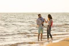 La jeune famille heureuse ont l'amusement sur la plage courue et sautent au coucher du soleil Images stock