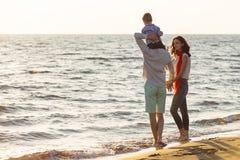 La jeune famille heureuse ont l'amusement sur la plage courue et sautent au coucher du soleil Photos libres de droits