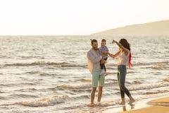 La jeune famille heureuse ont l'amusement sur la plage courue et sautent au coucher du soleil Photo stock